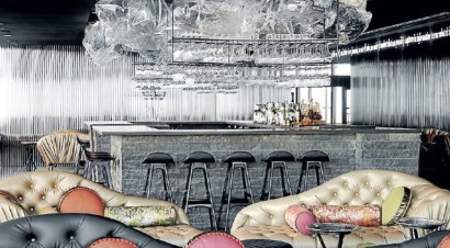 decretive lui cocktail bar with black bar stools, leather couches and hanging wine glasses