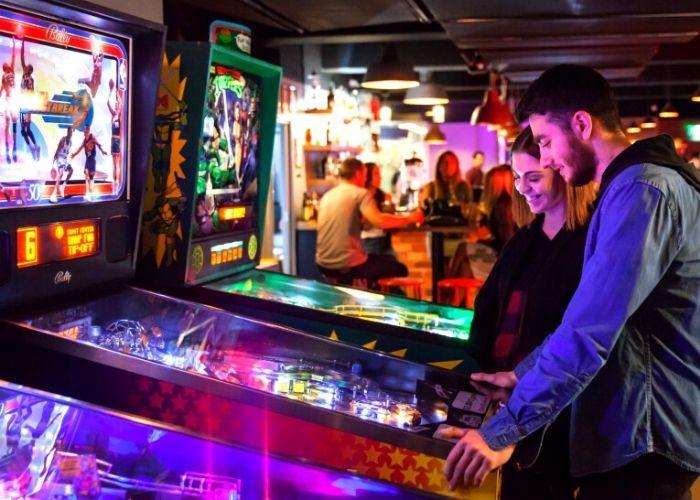 man and woman playing pin ball inside bartronica's hidden basement arcade on flinders lane in cbd