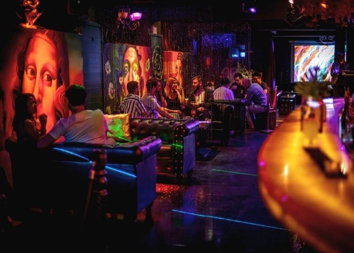 groups of people seated at dimly lit booths at Miranda bar and Lounge night club