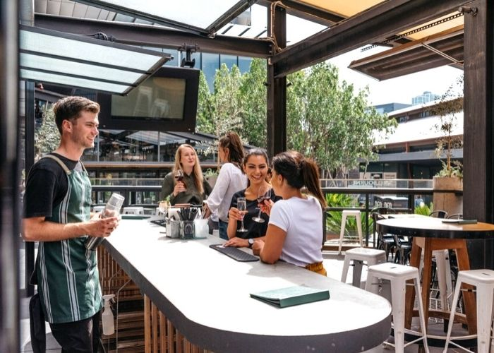 four women toasting wine glasses at melbourne public bar and waiter standing in south wharf