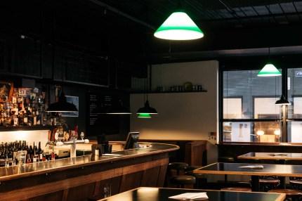 down light and woodern tables at saving grace bar