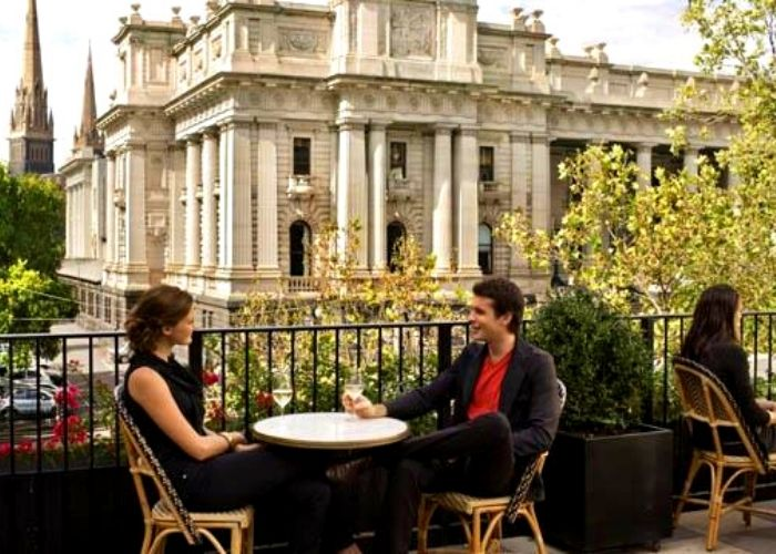 couple seated with wine glasses on Siglo rooftop with views of CBD trees and parliament house