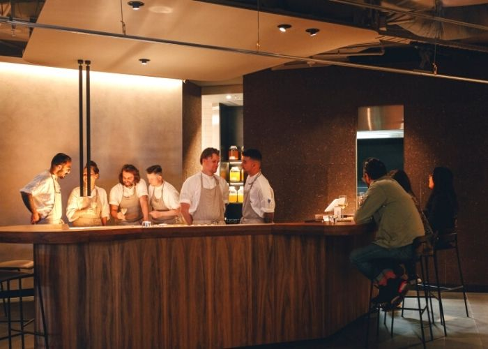 six bar staff in white shirts and aprons behind bar with two customers seated at Byrdi Australian restaurant