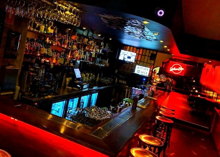 red neon lights in cbd dive spleen bar in cbd with bar stools beer wine and whiskey on 41 bourke street