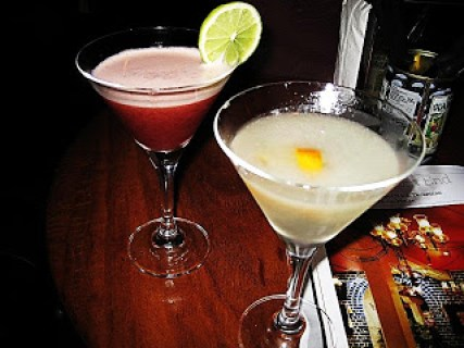 two cocktails one red and one yellow with a piece of lime