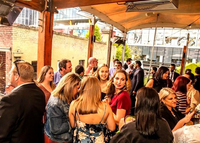 large crowd with beautiful women on top of the emerald peacock rooftop cocktail bar in city cbd
