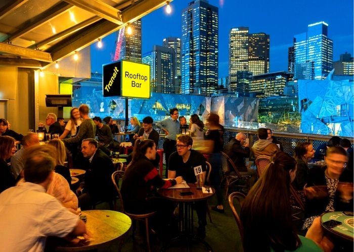 Melbourne cbd views over federation square from transit rooftop bar full of people dining  on top of transport hotel