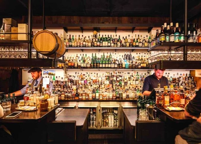 massive shelves lined with acholic bottles and two bar tenders and the whisky and alement