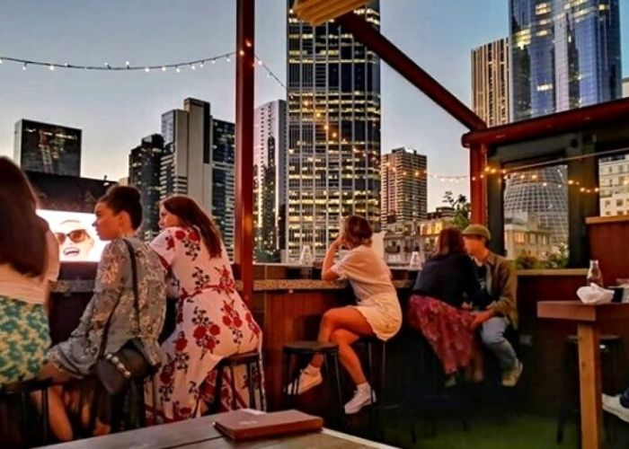 group of women overlooking melbourne city at night from goldilocks outdoor rooftop bar