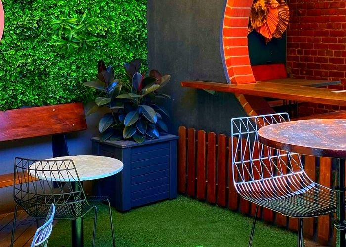 outdoor rooftop bar at young and jacksons swanston street with table, chairs and pants with green astro turf