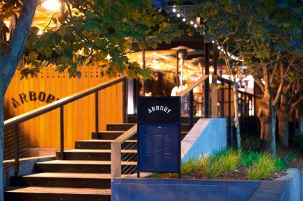 front stair entrance to arbory bar and eatery on flinders walk with trees and night lights