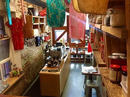 inside drystore cafe with hanging clothes and silks