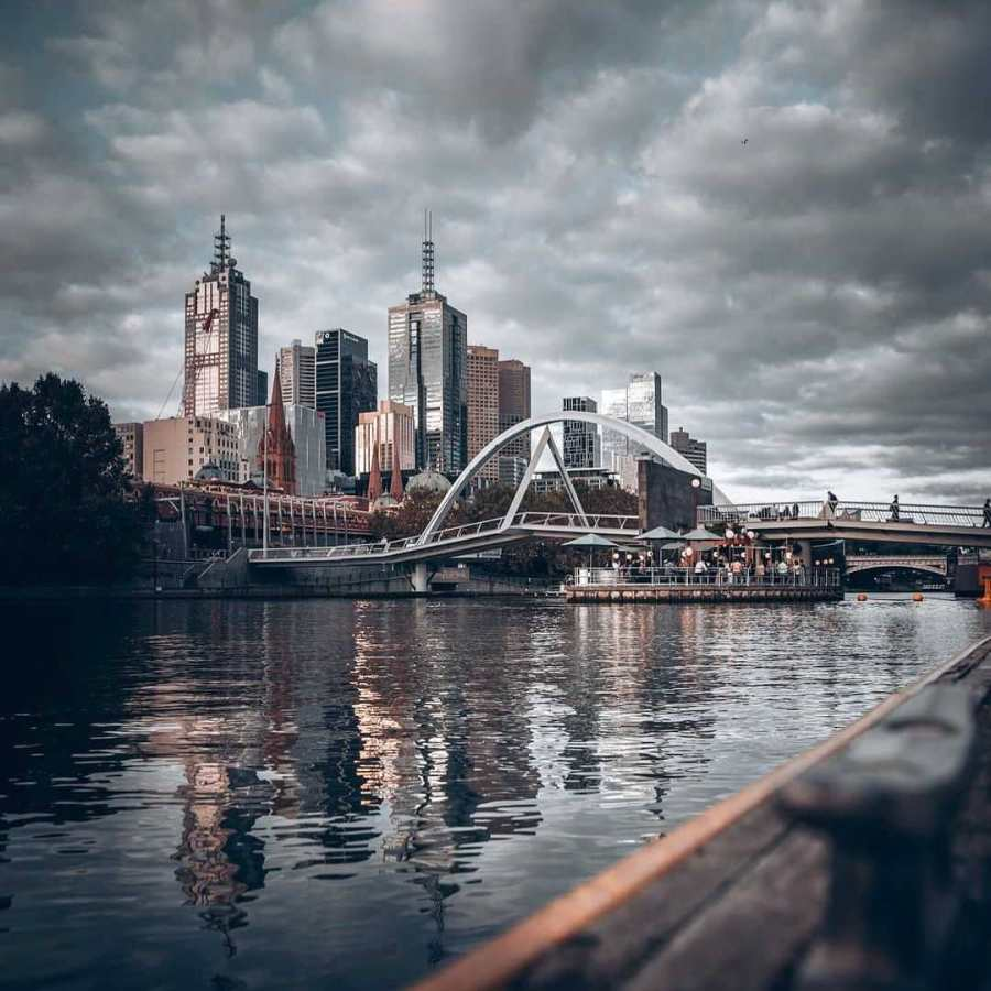 Even Walker pedestrian bridge with ponyfish island bar with melbourne cbd and flinders in back ground with grey cloudy skies