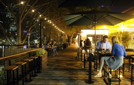 arbory riverside bar at night with couples dining outdoors under fairy lights