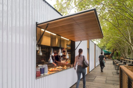 white container ship restaurant of arbory eatery with green trees and timber dining benches