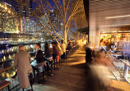 patrons seated and drinking along outdoor river side benches at night along arbory bar with yarra river in background