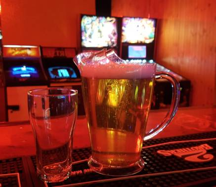 jug of beer and empty glass on bar with pinball machines in background