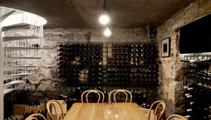 wine cellar basement with wooden dining table and large wine cellars filled with wine and white stairs