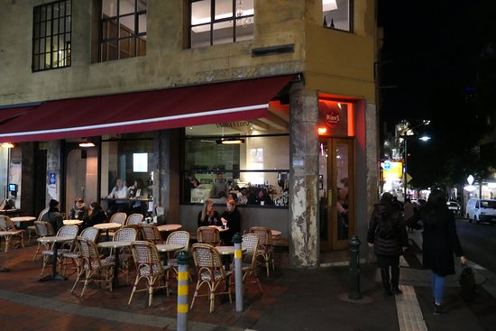 outdoor lane way dining at night with tables at chairs set up out front of Kirks on Hardware lane