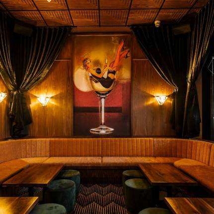 ornate booth at a bar with luxury couches, green curtains and painting of lady in a wine glass