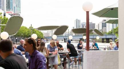 people seated at water front ponyfish cafe with food and drinks