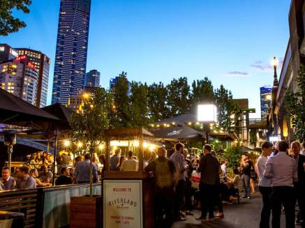 night time crowds drinking and eating at riverland beer garden with melbourne cbd in background