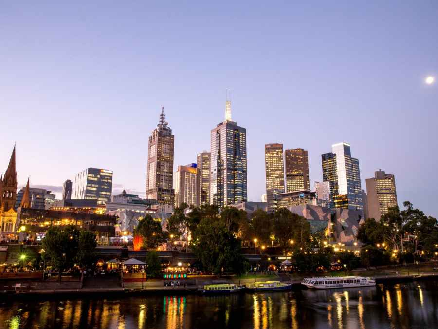 evening view of Melbourne CBD yarra river and riverland bar at night with bots in the river
