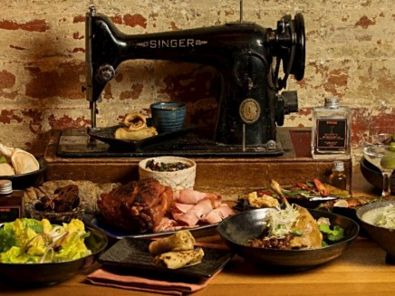 black singer sewing machine with plates of asian food