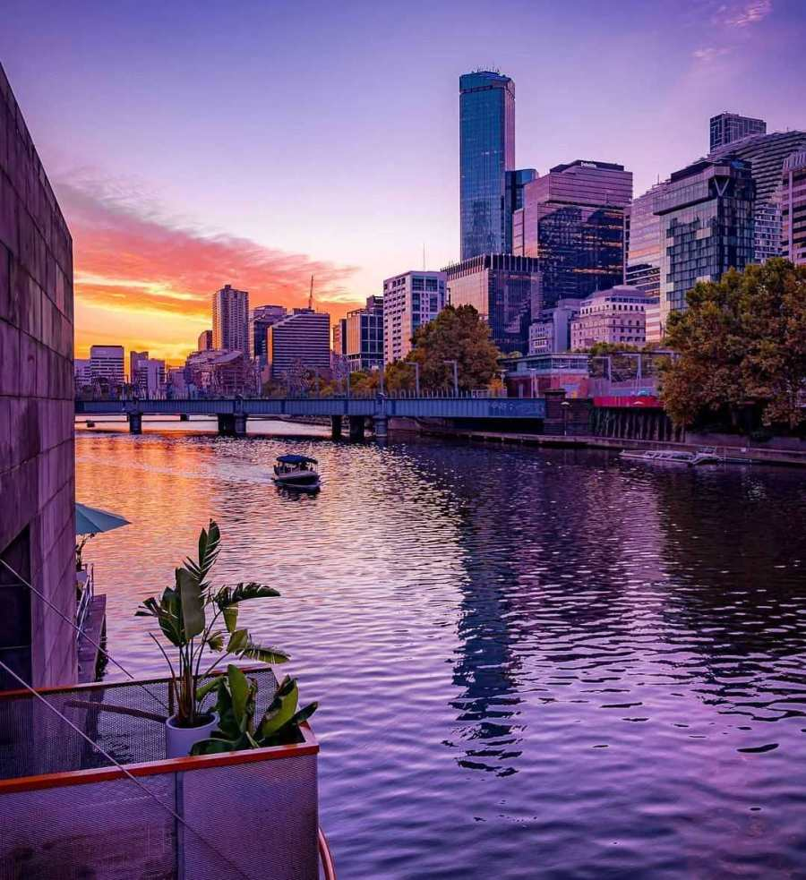 boat on yarra river with afternoon suns reflection and cbd buildings in background