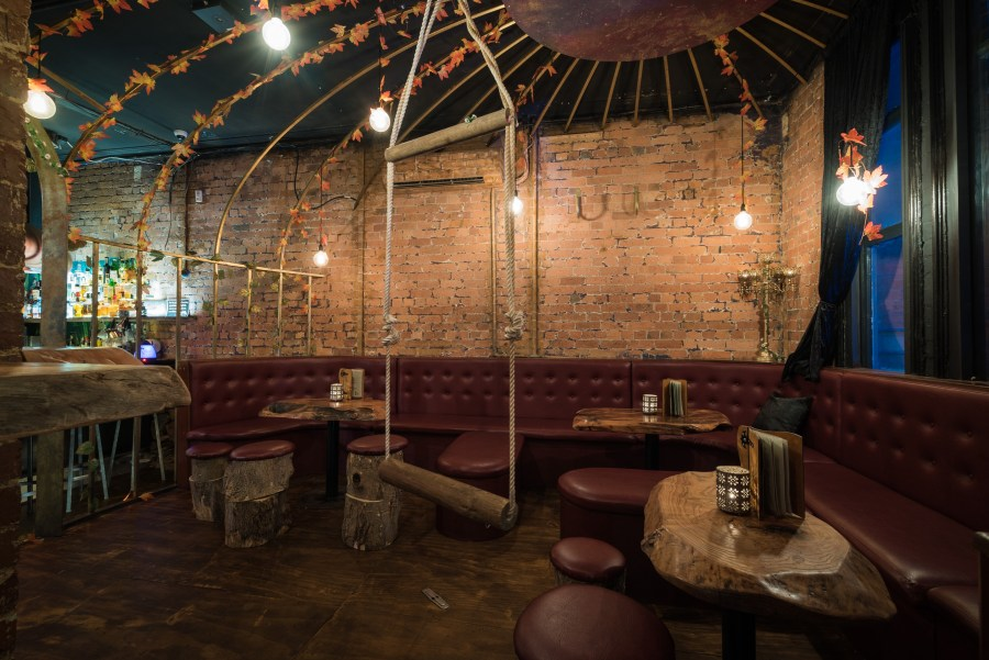 rope swing in fantasy bar set up with booths, small tables and brown bar stools