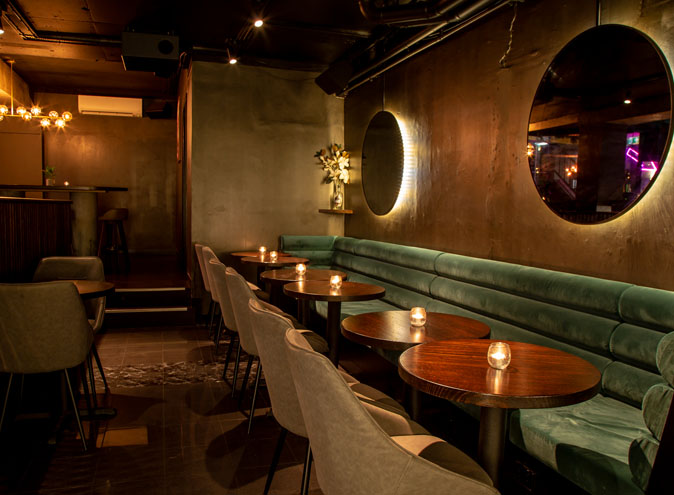 dining restaurant couches at clara with empty seats and candles on round wooden tables