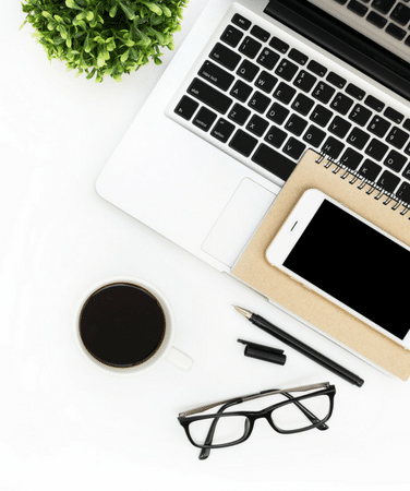 Top view of a white desk with a laptop, cell phone and eye glasses.