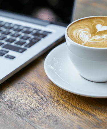 A closeup of a latte in a white mug next to a computer keyboard