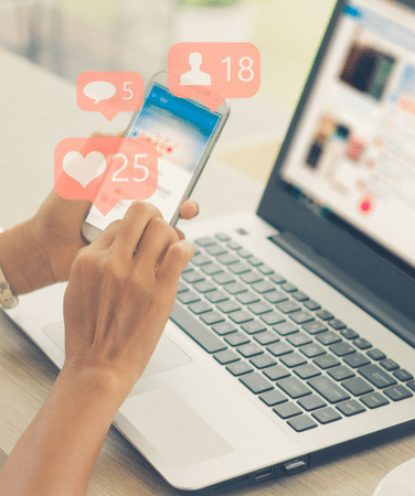 A woman is using a social media app on her mobile phone, displaying hearts, likes and friends