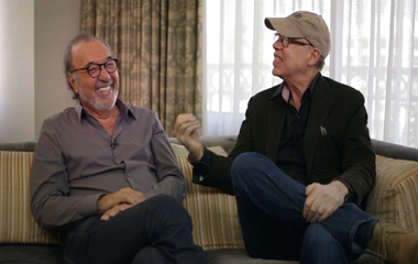 James L. Brooks and Larry Moss laughing on couch (380×240)