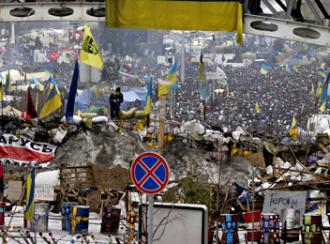 A dense crowd of protesters fill the streets beyond a barricade in Kiev (Christiaan Triebert)