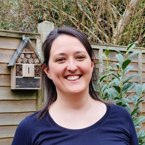 Kathryn smiling broadly at the camera, she is outside with an ant hotel on the fence behind her.
