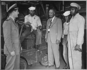 """Lester Granger, while inspecting facilities for Negro personnel at NAS, San Diego, CA, stops to chat with Rofes Herring, S1/c; Walter Calvert, S2/c; and Nollie H. Million, civilian employe[e], as Lt. Roper (left) stands by."""