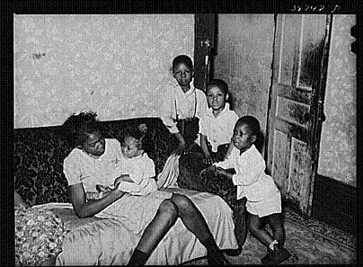 A black mother and her children spending time together; one of the families who received relief amidst pervasive discrimination by color in efforts to aid those in need.