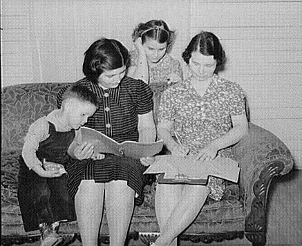 Young children look on as their mother and a worker go over a recordbook.