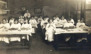Girls sit at tables working in this Sewing class at the University of Chicago Settlement Trade School, 1918