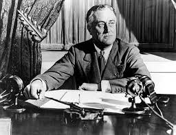 "President Roosevelt, seated at desk with microphones, prepares to give a ""Fireside Chat,"" Sunday, May 7, 1933"