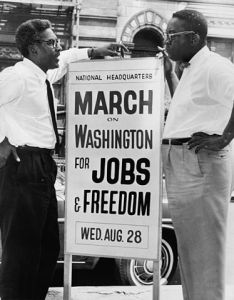 Bayard Rustin (left) and Cleveland Robinson (right), stand next to a sign identifying the National Headquarters for the March