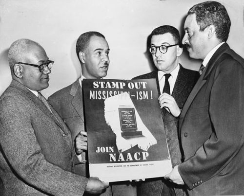 Holding a poster against racial bias in Mississippi in 1956, are four of the most active leaders in the NAACP movement: Henry Moon, Roy Wilkins, Herbert Hill, and Thurgood Marshall