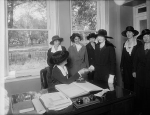 Women's Bureau, Police Department. One woman sits at a desk. Six others stand near her. All wear large hats.