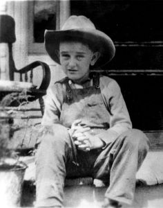 Lyndon Johnson as a child in overalls wearing a cowboy hat