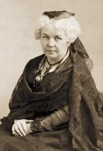 Photograph of Elizabeth Cady Stanton, seated with a dark lace mantilla. Her white hair is curly and she looks directly at the camera, her hands folded in her lap.