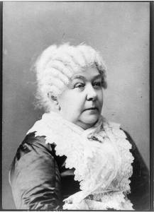 Photograph of Elizabeth Cady Stanton. Her white hair is curled and she wears lace over a dark dress. She is seated.