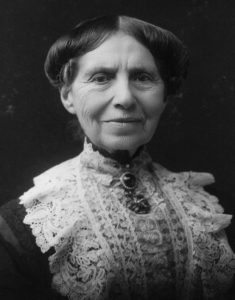 Photograph of Clara Barton smiling. She wears lace over her dark dress and a broach at her neck