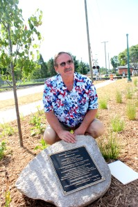 Ken Schippers kneels by the plaque installed on a boulder at the Trailhead entrance.